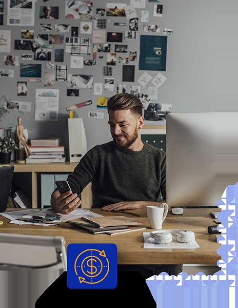 smiling man sitting at desk looking at smartphone